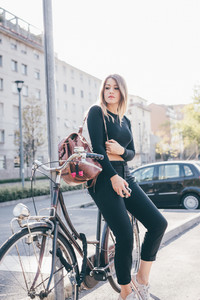 Young blonde caucasian woman sitting on her bike holding smart phone, pensive - student, serious, traveler pensive