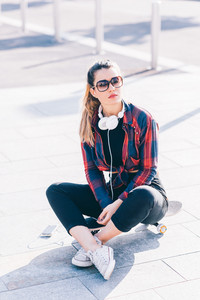 Young blonde caucasian woman sitting on her skateboard outdoor in the city wearing sunglasses - serene, music, sportive concept