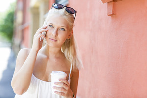 Young blonde girl talking on the phone outdoor