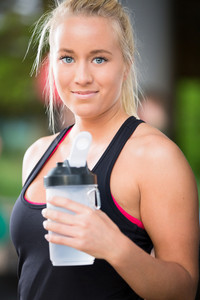 Young blonde woman drink water at fitness center