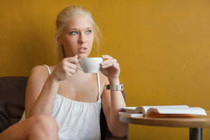Young blonde woman drinking coffee at cafe