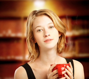 Young blonde woman holding a red coffee mug