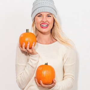 Young blonde woman holding pumpkins for halloween