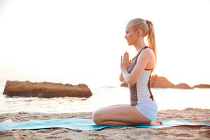 Young blonde woman meditating on the beach at sunset