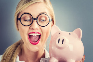 Young blonde woman with a piggy bank on a gray background