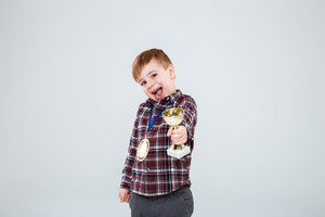 Young boy holding and presentation chalice with open mouth. Isolated gray background