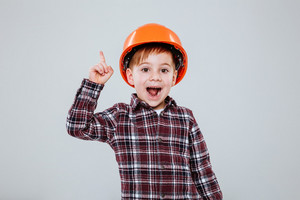 Young boy in helmet and shirt pointing up with open mouth. Isolated gray background