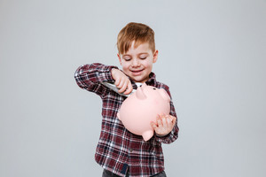 Young boy in shirt opening moneybox. Isolated gray background