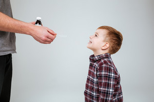 Young boy taking medications from father. Isolated gray background