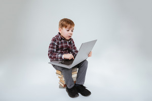 Young boy using laptop and sitting on books. Isolated gray background