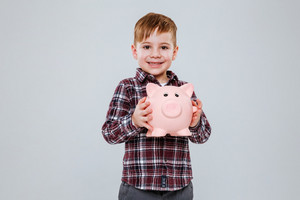 Young boy with moneybox in hands looking at camera. Isolated gray background