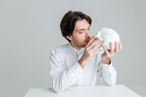 Young brunette man kissing fake skull isolated on the gray background