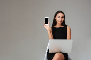 Young brunette woman in black dress sitting with laptop and showing blank screen mobile phone over gray background