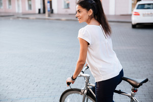 Young brunette woman riding on bicycle in city street