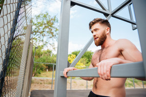 Young brutal bearded strong man doing sports exercises outdoors