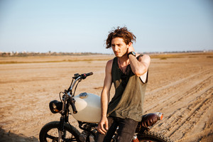 Young brutal man in black leaning on a motorcycle