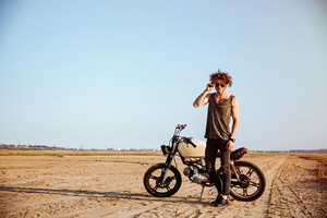 Young brutal man in black standing near a motorcycle at the desert