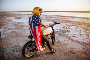 Young brutal man in golden helmet and american flag cape sitting on his motocycle looking away