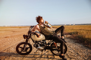 Young brutal man laying on his motorcycle in the desert and drinking water