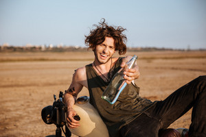 Young brutal man laying on his motorcycle in the desert and giving glass water bottle