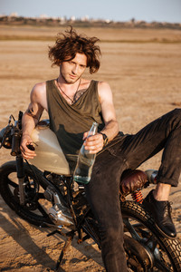 Young brutal man laying on his motorcycle in the desert and holding glass water bottle