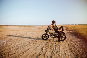 Young brutal man laying on his motorcycle in the desert and posing