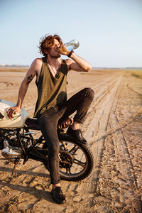 Young brutal man sitting on his motorcycle in the desert and drinking water