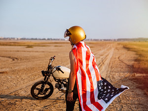 Young brutal man wearing american flag cape and golden helmet standing near a motorcycle at the desert