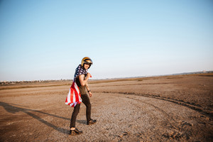 Young brutal man wearing american flag cape and golden helmet walking at the desert