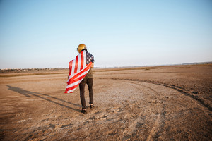 Young brutal man wearing american flag cape and golden helmet walking away at the desert