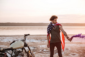 Young brutal man wearing american flag cape holding smoke bomb at the desert
