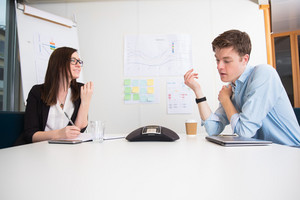 Young Business People Using Conference Phone At Desk