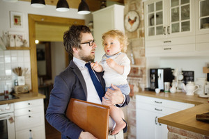 Young businessman coming home from the office, holding his little son in the arms.