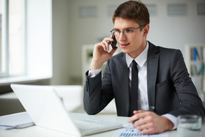 Young businessman in suit using laptop and calling in office