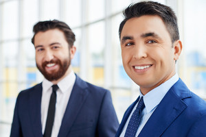 Young businessman looking at camera with toothy smile on background of his colleague