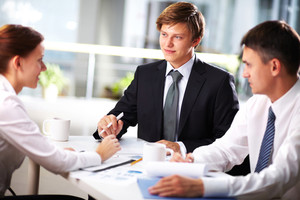 Young businessman looking at female during interview or negotiations
