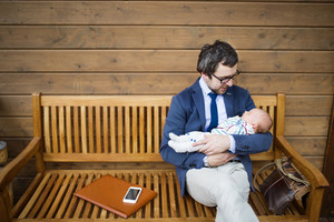 Young businessman with his little baby daughter sitting on wooden bench on front porch.