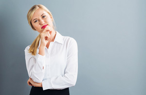 Young businesswoman in a thoughtful pose on a gray background