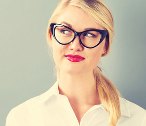 Young businesswoman in black glasses on a gray background
