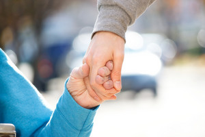 Young Caregiver Holding Senior's Hand Outside
