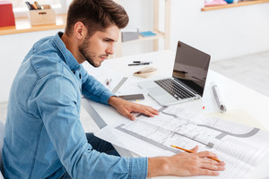 Young casual businessman working with documents while sitting at the office table