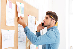 Young casual concentrated businessman looking at office task board and talking on the phone