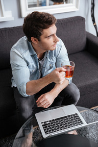 Young casual man drinking tea and working on laptop computer at home