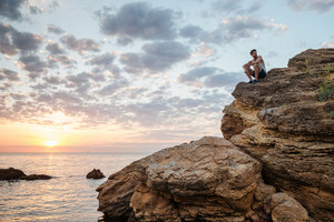 Young casual man sitting on the mountain rock by the sea and looking at sunset