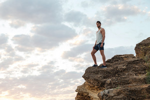 Young casual man standing on the mountain rock by the sea and looking at sunset