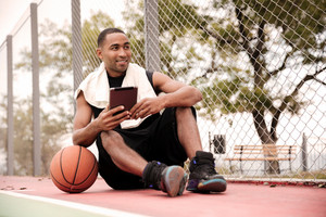 Young cheerful african basketball player sitting in the park near basketball and holding tablet. Look aside.
