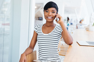 Young cheerful african businesswoman talking on the mobile phone at office