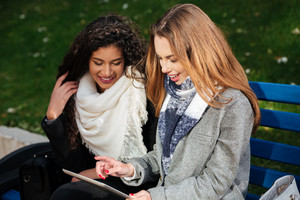 Young cheerful caucasian and african women wearing scarfs sitting on a bench outdoors. Looking at tablet.