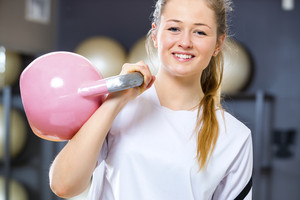 Young cheerful woman holds kettlebell at fitness gym center