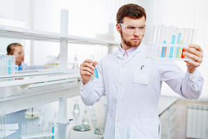 Young chemist looking at flasks with liquid chemical substances